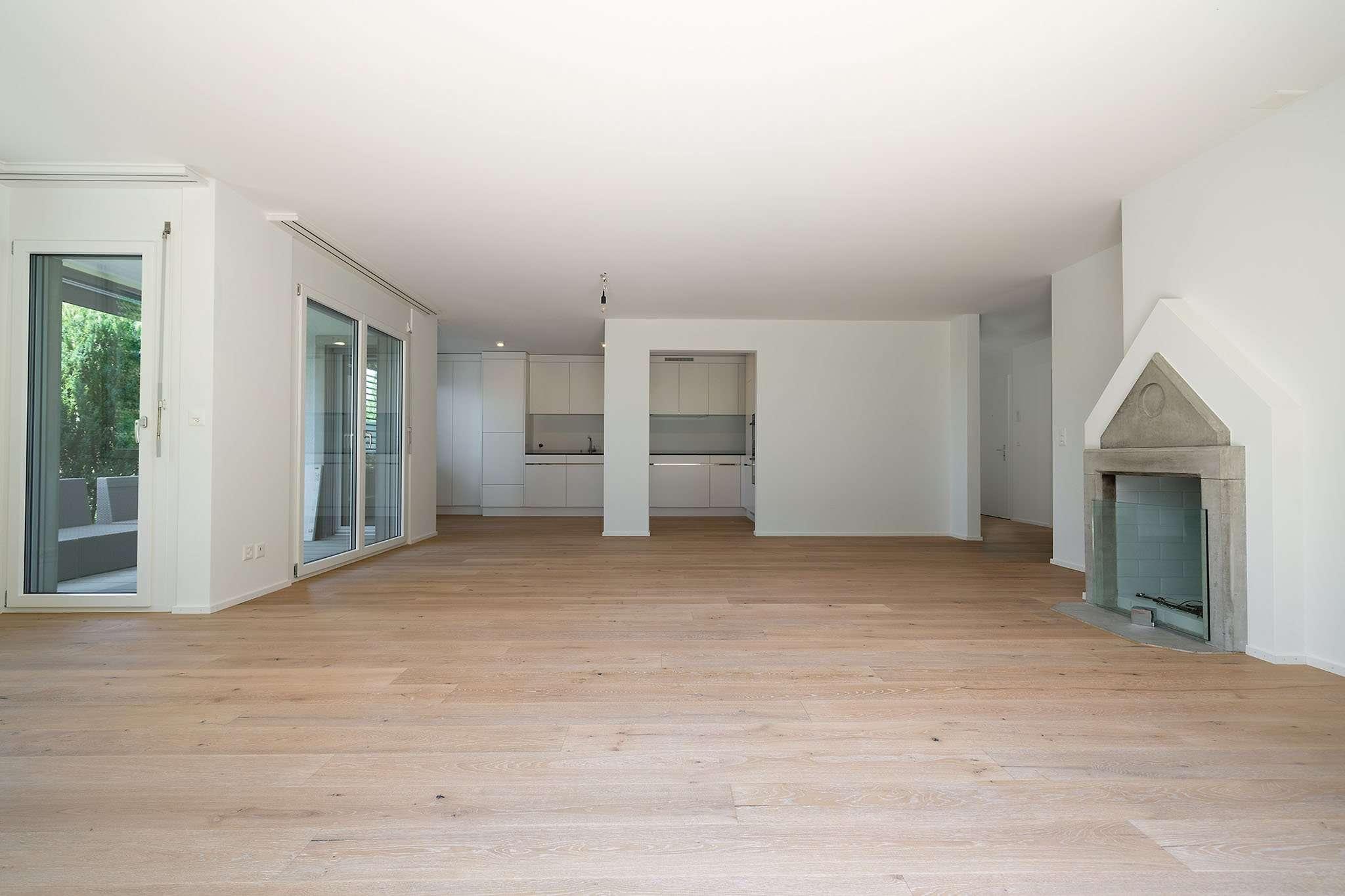 Weiträumiges, weiß gestrichenes Wohnzimmer mit Kamin